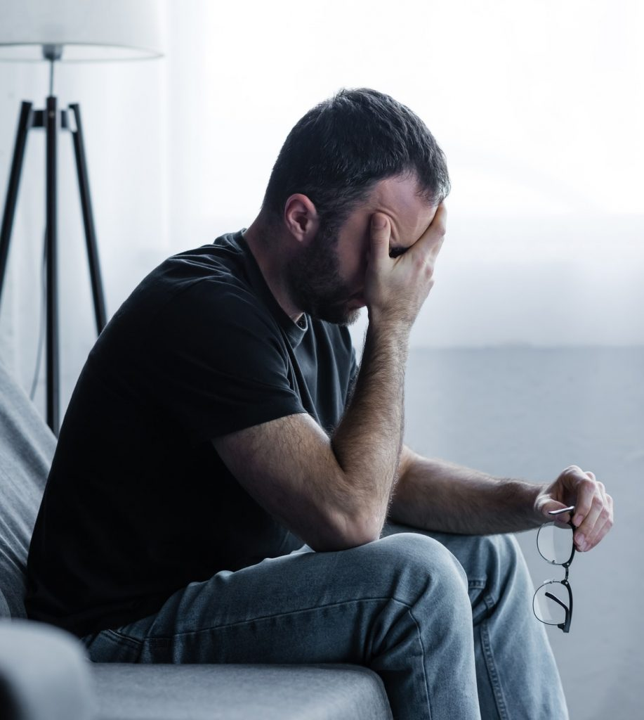 depressed man holding glasses while sitting on sofa and covering face with hand